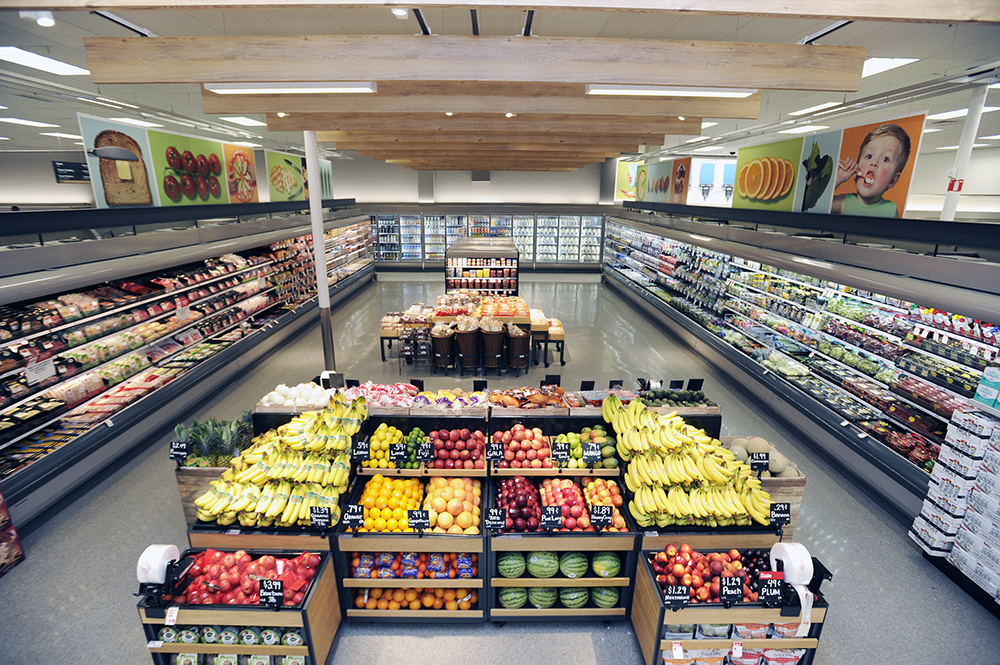 wide grocery aisle features wooden boxes full of fresh fruits and refrigerator cases on the sides