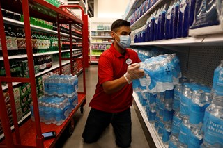 A team member in a red shirt, jeans and mask lifts a package of bottled water onto a shelf