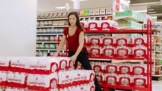 female team member in red shirt and jeans loads packages of Market Pantry bottled water on an endcap
