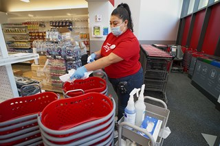 A team member in a red shirt, blue jeans, blue fask mask and blue gloves sanitizes shopping baskets outside a store entrance.