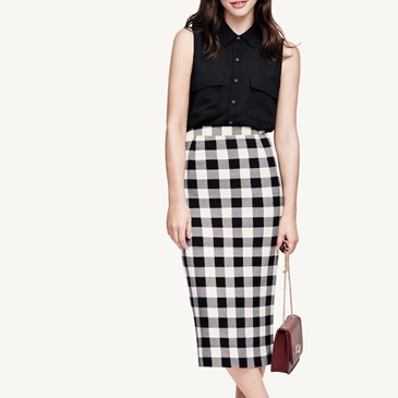 Model wearing black top, black and white checkered pencil midi skirt, brown bag, black heels