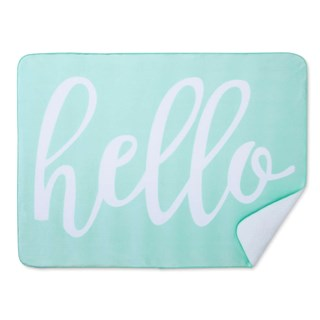A sea foam green blanket with rounded edges and white text: