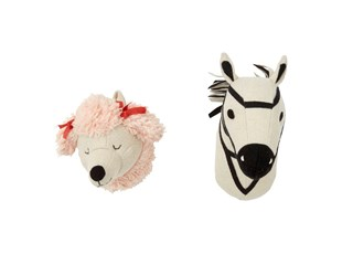 A pink plush poodle head and a black and white plush zebra head wall mounts