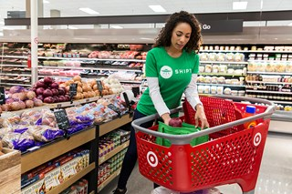 A woman in a green Shipt shirt puts groceries in a cart