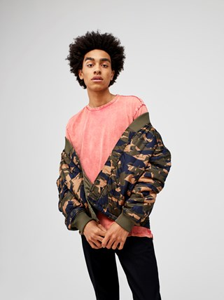 A man wears a coral t-shirt and camo jacket with dark jeans