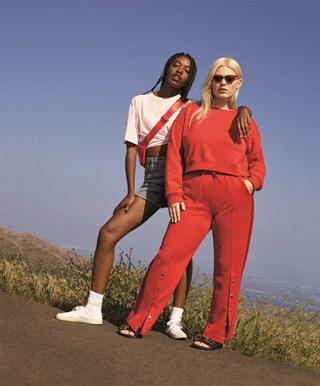Two women, one wearing a red top and pants and another in a t-shirt and shorts