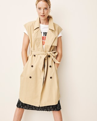 A model wears a tan sleeveless trench coat over a white graphic tee and black skirt
