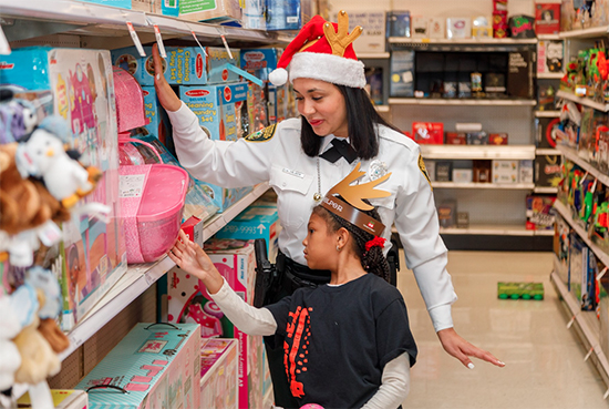 A police officer in uniform and a little girl shop together for toys