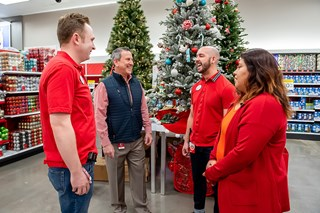 Brian Cornell stands in a semi-circle talking with three store team members in front of holiday disp