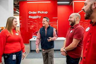Target CEO Brian Cornell talks to three Team Members in a store, all wearing red, denim and khaki