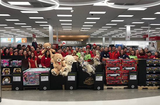 A large Target store team poses together near displays of toys