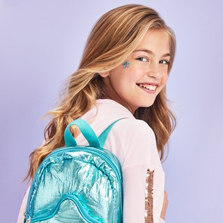 A tween girl wears a teal shimmery backpack
