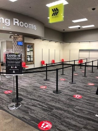 A carpeted area outside the fitting rooms at a Target store, dotted with distancing stickers on the floor and stanchions to define where the line goes.