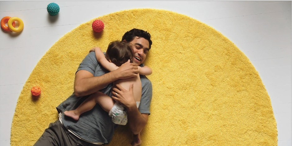 Father hugging his toddler child on top of a yellow circular rug with toys scattered around