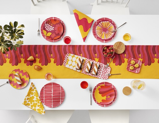 white table with red and yellow table cloth, red and yellow patterned plates and napkins, silver utensils, strawberries, cake