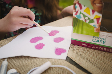 Daughter painting pink hearts on a piece of paper for a Seedling project