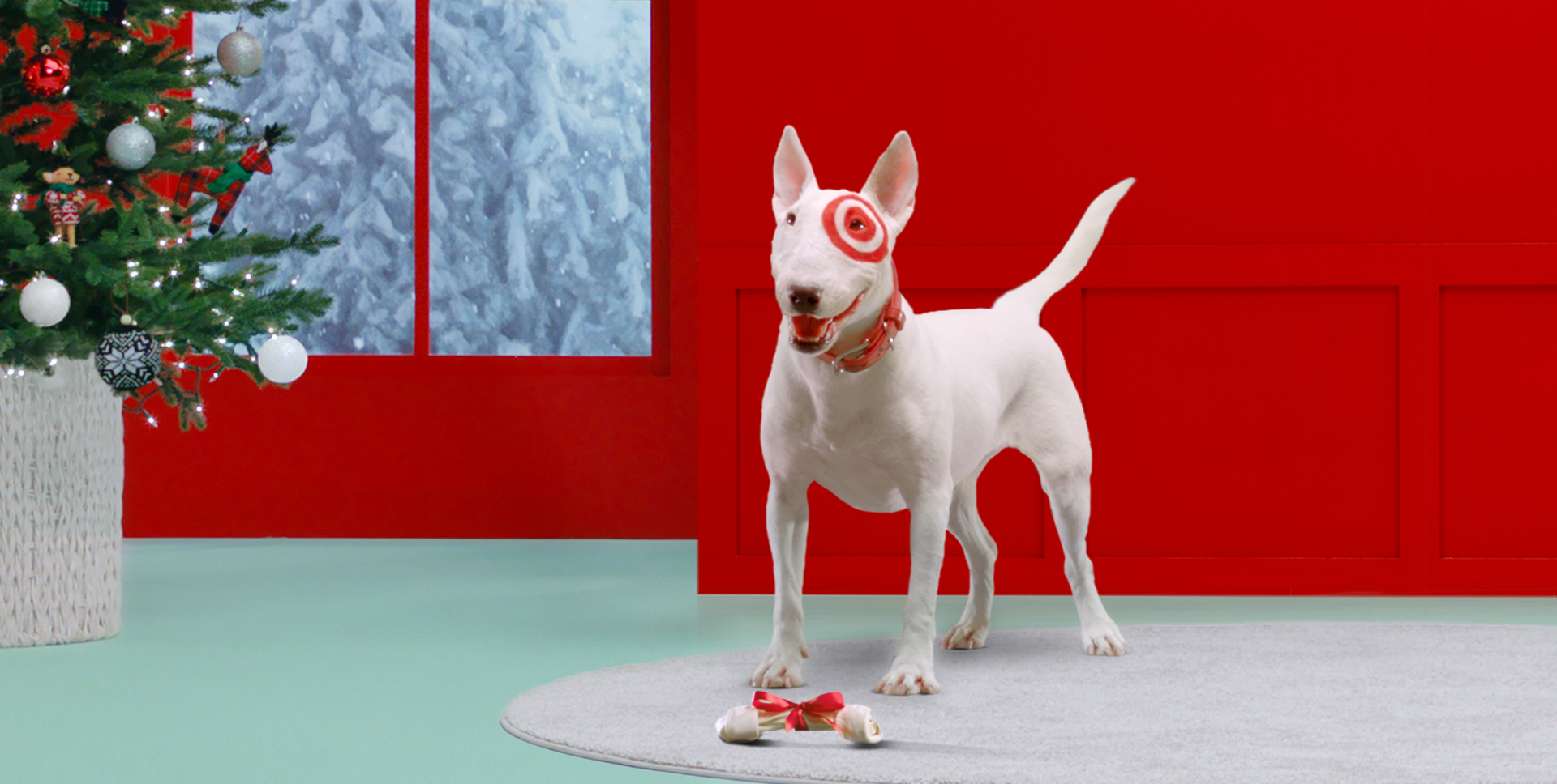 Two kids and a Bullseye puppy lay on a red background with toys and the bullseye logo