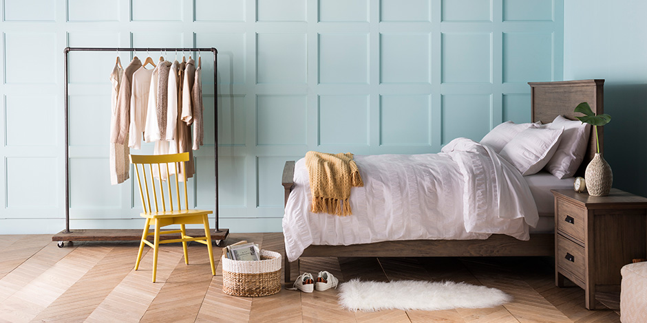Light and airy bedroom with blue paneled walls, a wooden bed and nightstand with white bedding