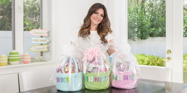 Barbara Bermudo standing behind the three completed Easter baskets for her daughters