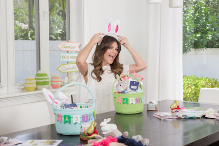 Barbara Bermudo creating Easter baskets at her table and trying on a bunny ears headband.