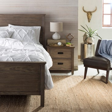 Neutral bedroom with wooden bed and nightstand, white bedding and knit rug, leather chair with throw