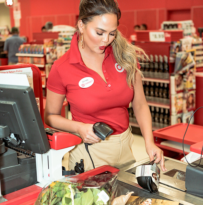 Chrissy Teigen wears red and khaki and scans items at a Target cash register