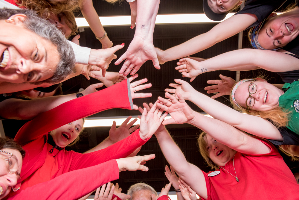 A group of smiling team members huddle up with their hands in a circle