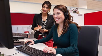 A woman smiles as she types at a keyboard while another woman stands behind her taking notes