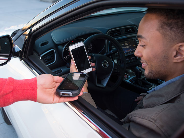 a guest sits in driver's seat of car, looking at phone while team member scans with his device