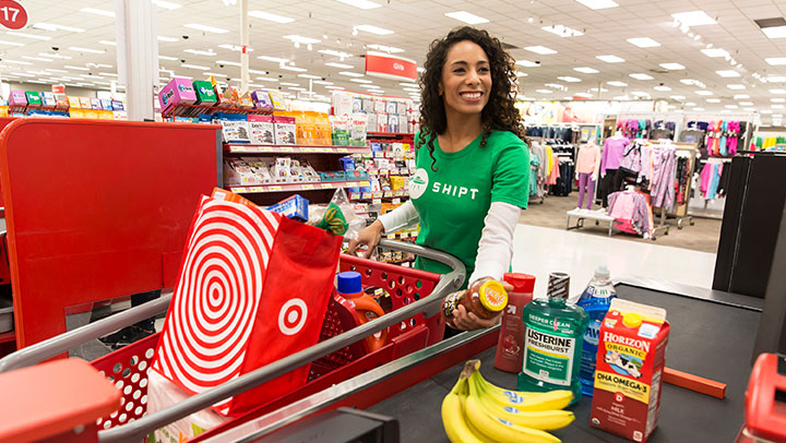 female Shipt shopper in green shirt places items on checkout conveyer belt: bananas, milk, listerine