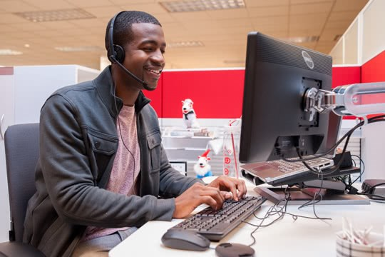 Target finance team member on a telephone at their computer