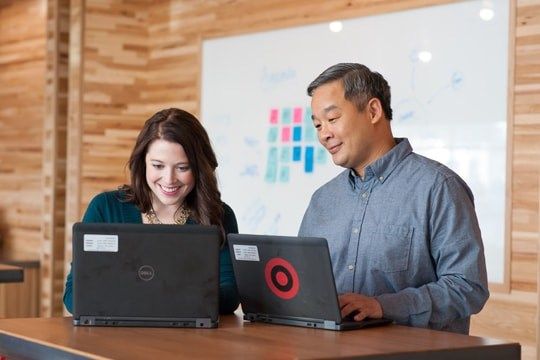 Two Target team members working on their laptops