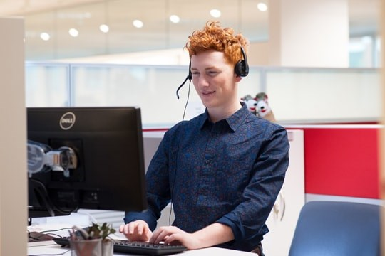 Target team member on phone at computer