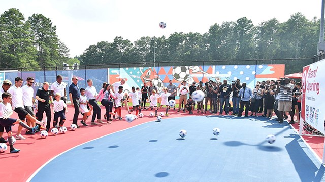 kids and adults kick soccer balls at the opening of a community soccer playspace