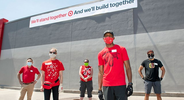 Five team members in masks stand, distanced, in front of a Target store