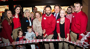 Team members and family members cut the ribbon in front of their new store