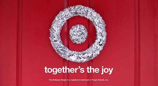 A silver tinsel wreath on a red door with text reading Together's the Joy