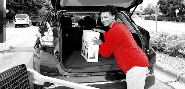 image of a woman loading a product into her car