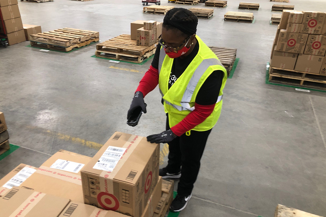 A team member in a yellow vest and red mask packs boxes at our Mixing Center in Minneapolis
