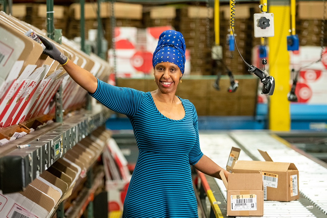 A DC leader in a blue striped dress and blue head scarf sorts products into bins in the warehouse