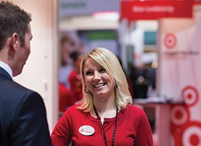 A Target team member talks to an attendee at the Reaching Out LGBT MBA conference