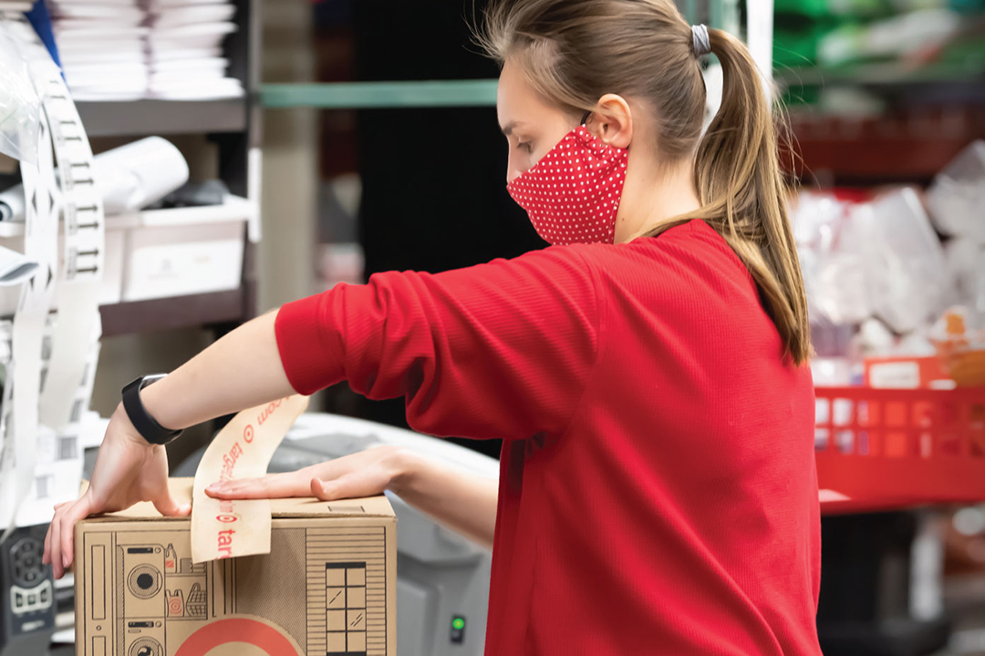 A team member in a red shirt and face mask tapes a cardboard box with Target illustrations