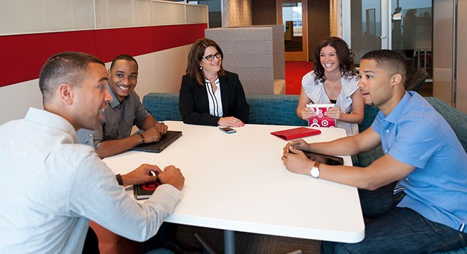 Target team members sit around a table during a meeting
