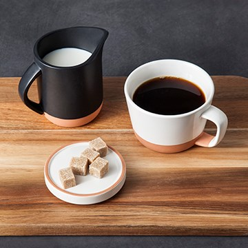 On a wooden tray, a white clay mug filled with coffee sits next to a black pot of cream and a white plate with sugar cubes.