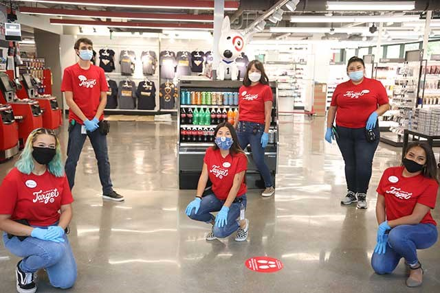 Six Target team members pose in a store, socially distanced and wearing masks and red Target t-shirts.
