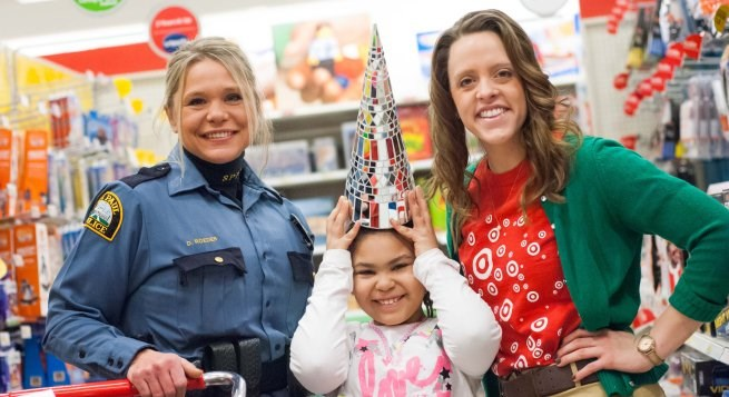 a kid holiday shopping with a police officer and team member
