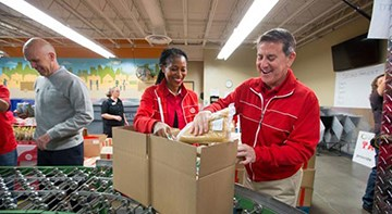 Target's Laysha Ward and Brian Cornell pack boxes of donations at a volunteer event