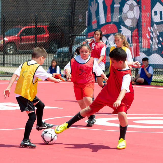 three kids play soccer in red and yellow jerseys on a Target pitch