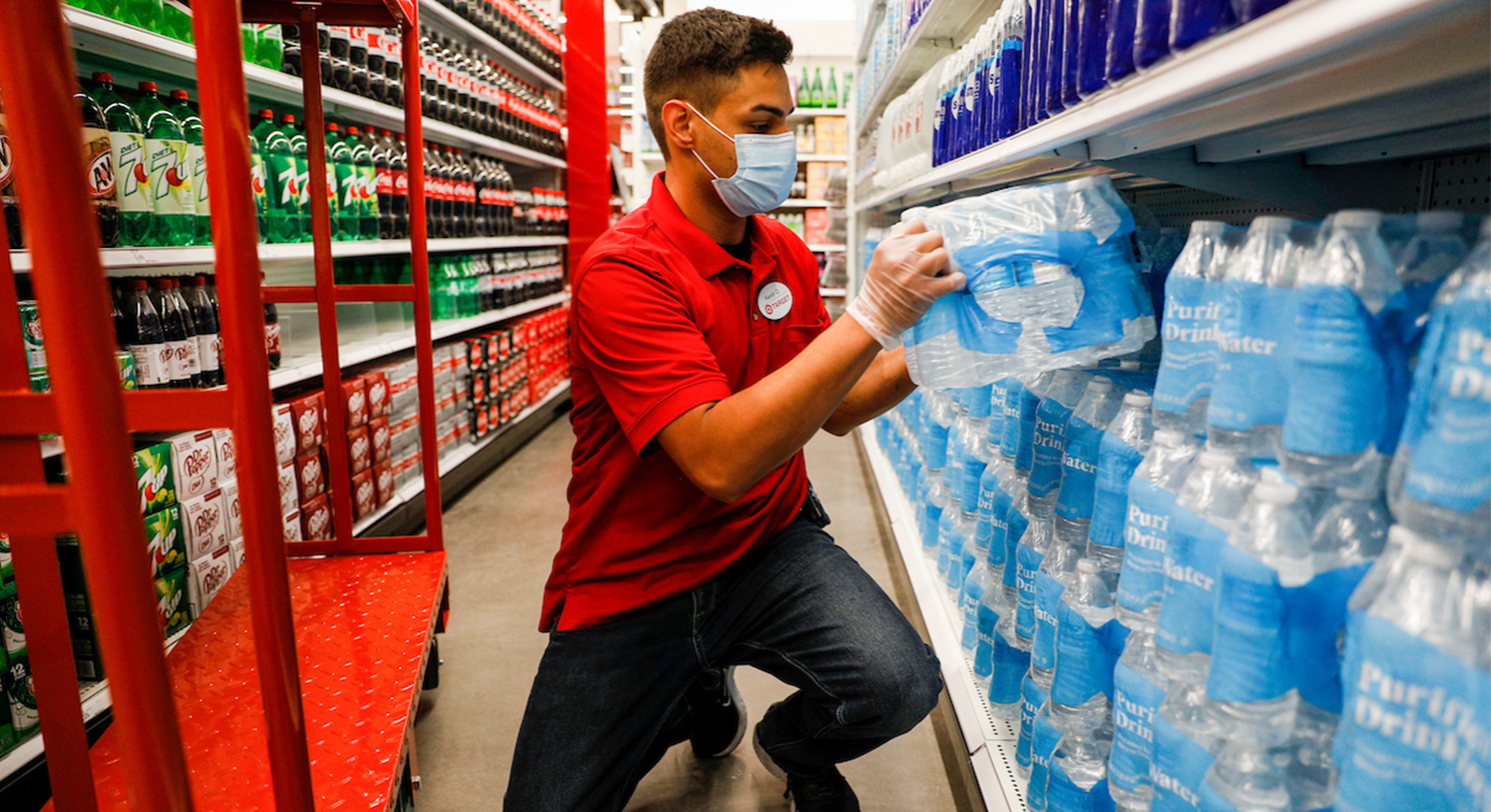 A team member in a red shirt, jeans and mask stocks packages of bottled water on a shelf