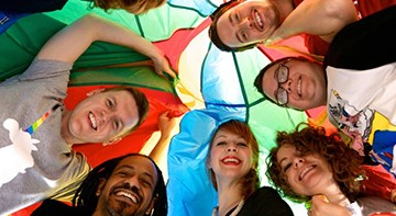 Five team members in a circle under a multicolored parachute.